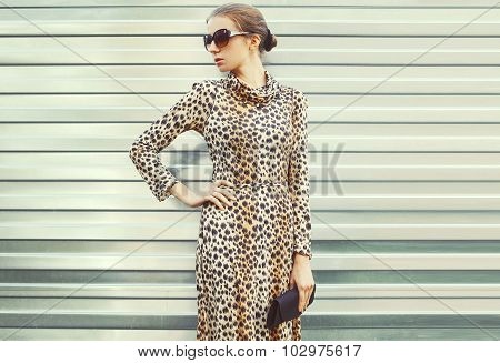 Fashion Pretty Woman In Sunglasses And Leopard Dress With Handbag Clutch Over Metal Background, View