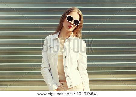 Fashion Stylish Woman In Sunglasses And White Denim Jacket Over Metal Textured Background