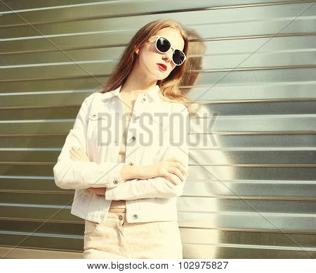 Portrait Fashion Young Woman In Sunglasses And White Denim Jacket Over Metal Textured Background