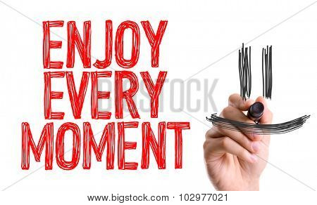 Hand with marker writing: Enjoy Every Moment