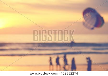 Blur People Relax On Tropical Sunset Beach With Parachuting Boat Abstract Background.travel Concept.