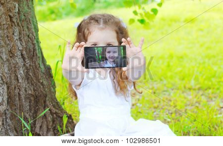 Child Making Self Portrait On Smartphone In Summer Park, Screen View