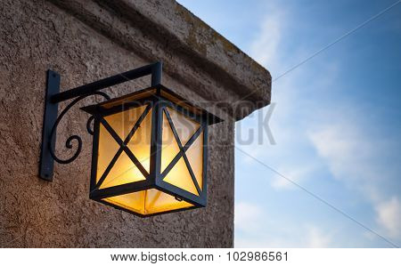 Street Lamp Mounted On Stone Wall Over Blue Sky