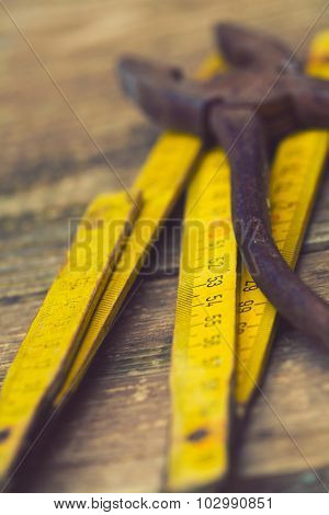 Old rusty pliers and wooden meter, retro style artistic photo with shallow DOF