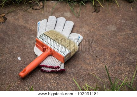 gloves and brush on a metal plate