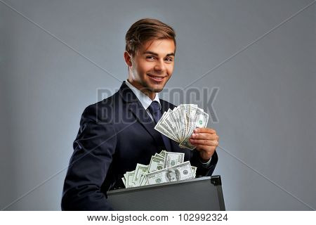 Elegant man holding case with money on gray background