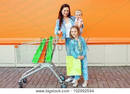 Happy Mother And Two Children With Trolley Cart And Colorful Shopping Bags