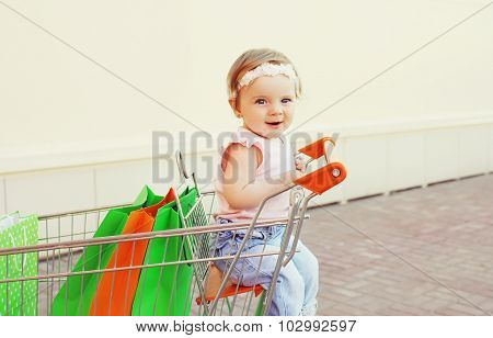 Happy Smiling Baby Sitting In Trolley Cart With Colorful Shopping Bags