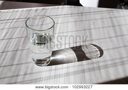 Glass Of Water Lightened With Sun On A White Table