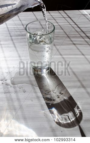Pouring Water In A Glass Lightened With Sun On A White Table