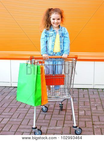 Happy Smiling Child In Trolley Cart With Colorful Shopping Bags