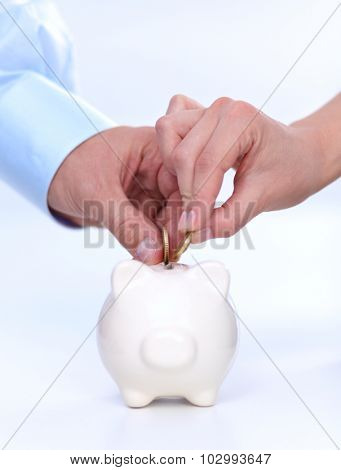 People putting coin into the piggy bank