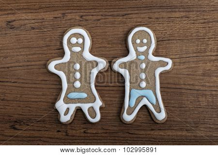 Gingerbread man and woman on a wooden background