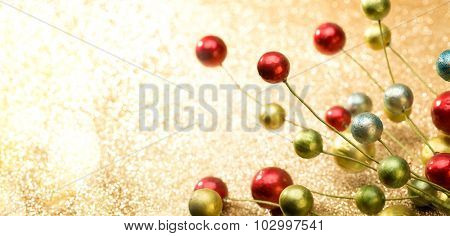 Christmas branch on background of defocused golden lights.