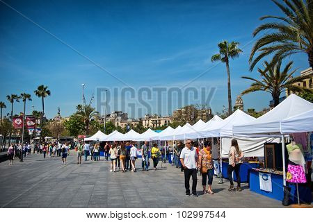 BARCELONA, SPAIN - MAY 02: Promenade / esplanade at the harbour of Barcelona, Spain. Little shops are selling their souveniers to tourists. May 02, 2015