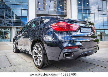 GDANSK, POLAND - SEPTEMBER 3 , 2015: New model BMW X6 in dark blue against modern design buildings in Gdansk. BMW is a German automobile, motorcycle and engine manufacturing company founded in 1916.