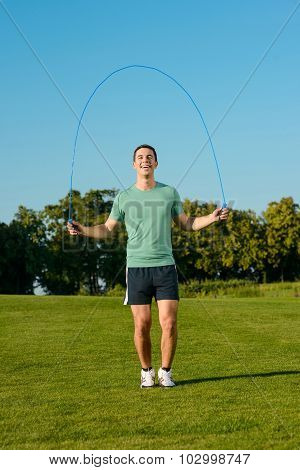 Guy jumps on a skipping rope on a green meadow.