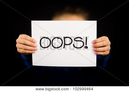 Child Holding Oops Sign