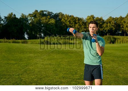 Guy with dumbbells on a lawn.