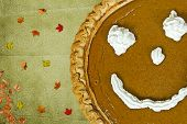 image of pie-in-face  - Happy face on a pumpkin pie for Thanksgiving - JPG