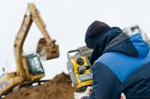 foto of theodolite  - surveyor worker with geodesy equipment device theodolite at land surveying outdoors - JPG