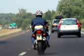 image of unclothed  - man riding on a motorcycle on a highway with the back of his shirt blown upward - JPG