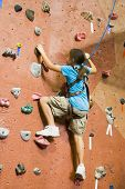 image of climbing wall  - a young girl climbing a tall indoor man - JPG
