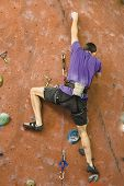 picture of climbing wall  - a man climbing a tall indoor man - JPG