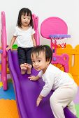 Постер, плакат: Asian Chinese Little Sister And Brother Playing On The Slide