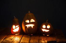 stock photo of jack o lanterns  - Jack o lanterns Halloween pumpkin face on wooden background and autumn leafs - JPG