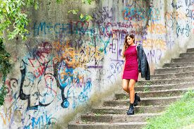 picture of mural  - Young woman with jacket over his shoulder down staircase next to murals - JPG