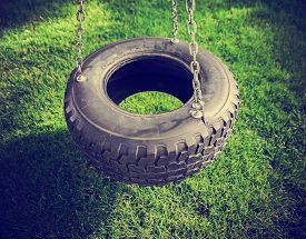 foto of tire swing  - an old rubber tire swing on chains in a backyard for kids to play on toned with a retro vintage instagram filter app or action effect  - JPG