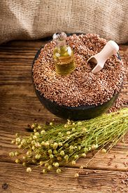 picture of flax seed oil  - Vertical photo with a bunch of flax plants with dried blooms bonded by natural cord placed on old wooden board and with burlap around which is near to bottle with flax oil and heap of flax seeds - JPG