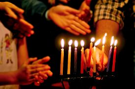 image of hanukkah  - A family is lighting a candle for the Jewish holiday of Hanukkah that is observed for eight nights and days.