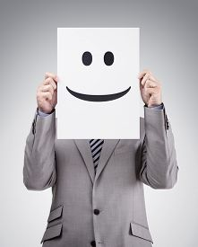 pic of emoticon  - Businessman holding and hiding behind a card with smiley face emoticon - JPG