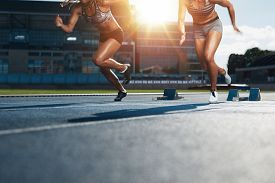 stock photo of sprinters  - Sprinters starts out of the blocks on athletics racetrack with bright sunlight - JPG