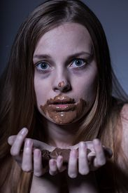 picture of bulimic  - Close up of a thin frightened teenager gorging on chocolate - JPG
