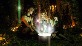 stock photo of cauldron  - Three beautiful witches are looking in to the magic cauldron - JPG