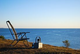 image of thermos  - Chair and basket with a thermos by the coast at summer evening - JPG