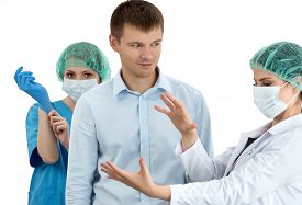 picture of proctoscopy  - Female doctor in cap and face mask putting on blue protective glove standing behind the scared patient - JPG