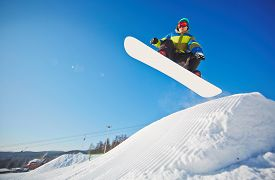 picture of snowboarding  - Active young man on snowboard hanging over snowdrift - JPG