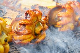 foto of cuttlefish  - Cuttlefish grilled on barbecue fire with smoke - JPG