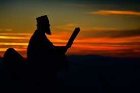 pic of priest  - silhouette of priest reading in the sunset light - JPG