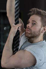 image of strongman  - Young sexy strongman with big muscles climbing the rope - JPG