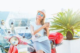 picture of takeaway  - Happy young trendy woman drinking takeaway coffee near her red moped on the waterfront in the morning - JPG