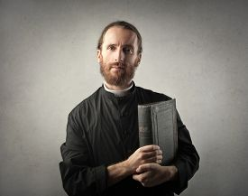 foto of priest  - Priest holding a Bible - JPG