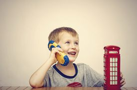 picture of phone-booth  - Boy talking on the phone and vintage british red telephone booth - JPG