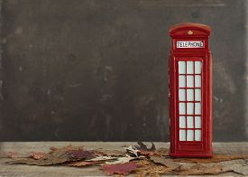 picture of phone-booth  - Autumnal image with dry maple leaves and red british vintage phone booth - JPG