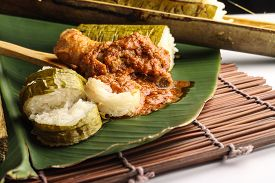 picture of malay  - malay lemang served with rendang ayam on banana leaves