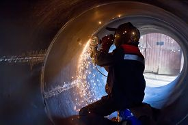picture of welding  - The welder carries out mechanical cleaning of the root surfaces of the weld seam to continue the weld multipass weld - JPG